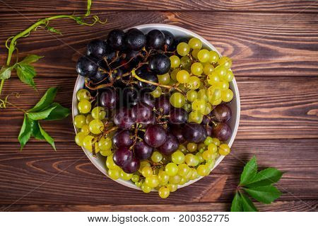Top View Bowl Of Various Grapes: Red, White And Black Berries And Few Green Leaves On The Dark Woode