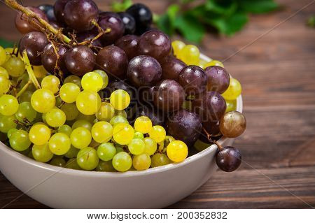 Close Up Bowl Of Various Grapes: Red, White And Black Berries On The Dark Wooden Table. Selective Fo