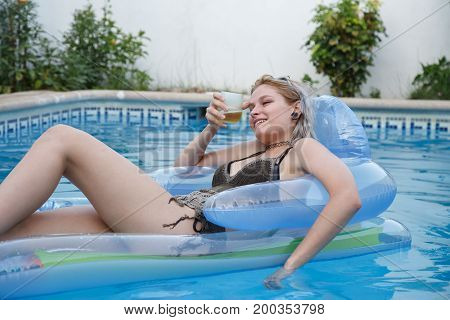 Young attractive woman lying on airbed and relaxing with beer in pool.