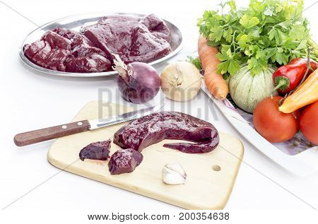 Raw liver and vegetables on a table close-up
