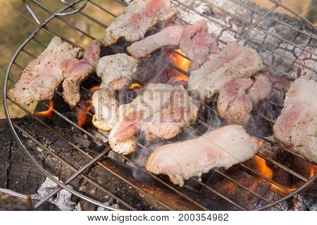 Some slices of Bacon being grilled, outdoors