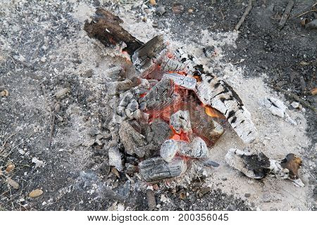 A Bonfire burning out, with ash around it