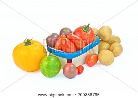 Assortment organic vegetable colorful tomatoes and potatoes isolated on white background