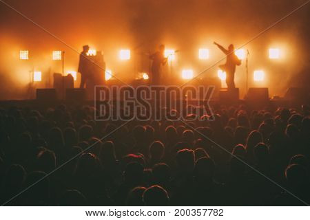 Rock band on a stage in a backlights in front of the crowd of big music festival