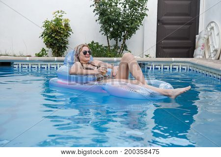 Young smiling woman lying on airbed and relaxing with beer in pool.