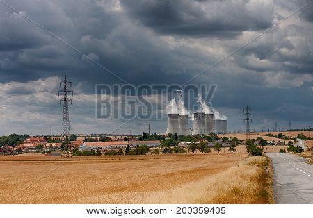 Aerial View Of Nuclear Power Station With Cooling Towers Against Cloudy Sky