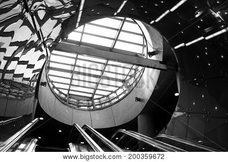Look up to the futuristic escalator in modern building. Black and white abstract background photo