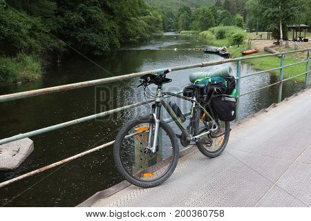 Mountain bike with saddlebags on the bridge . Camping equipments is mounted on the bike.