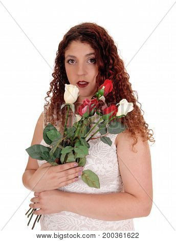 A beautiful young woman in a beige dress standing isolated for white background holding a bunch of roses waist up