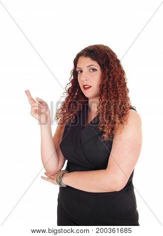 A young business woman stand in in a black dress with her finger crossed looking into the camera isolated for white background