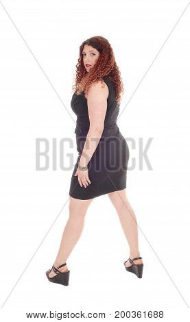 A beautiful Caucasian woman standing in a black dress from the back looking over her shoulder isolated for white background