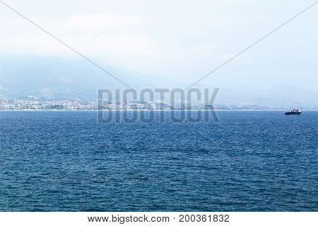Quiet sea surface and city landscape in the distance (Alanya, Turkey).