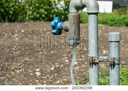 water valve pipe with running water in garden hot summer