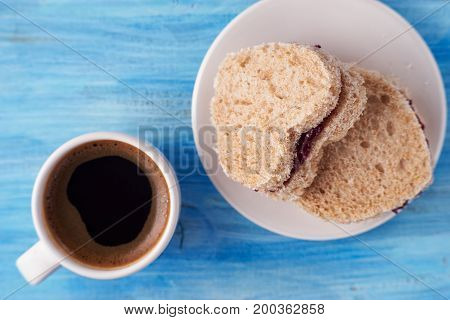 Top view of cup of espresso and heart shaped sandwiches with red jam
