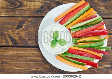 Top view of vegetable sticks on white plated and wooden table