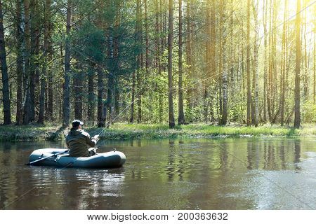 A fisherman in a boat on the river casts a fishing pole
