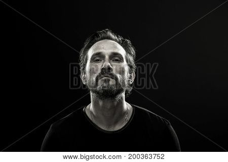 Portrait of brutal man on black background. Mid aged beardy man showig sad emotion.