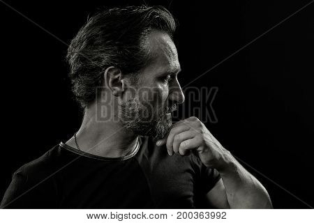 Black and white portrait of experienced male with emtions of pain and struggle. Side view of a beardy man holding fist close to chin.