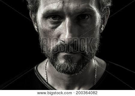 Close up portrait of seriously looking mature man. Black and white portrait of beardy male.