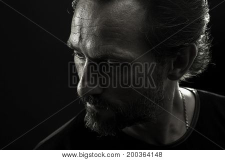 Monochrome portrait of strong man turnig face to left side. Close up view of mature wrinkled male showing emotion of frustration and troubleness.