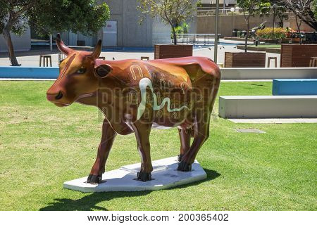 WESTERN AUSTRALIA, PERTH - NOVEMBER 2016: Brown painted cow in front of WA State Library as part of CowParade event