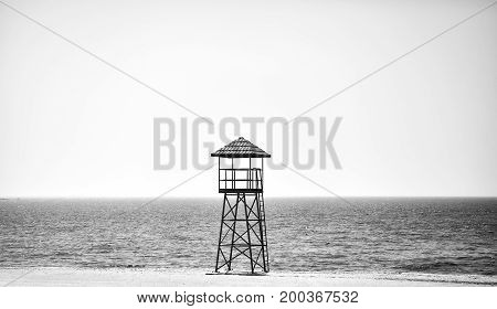 Black and white picture of a lifeguard tower on an empty beach.
