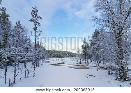 Snow covered norwegian lake and forest with light blue sky and clouds in Finnskogen, Hedmark