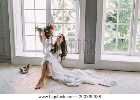 Cheerful, Young Bride Holds A Rustic Wedding Bouquet With Peonies On Panoramic Window Background. Cl