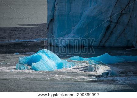 A piece of glacier floats in the water. A piece of ice floats next to the blue glacier. Part of the blue glacier is washed by waves.