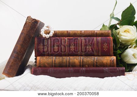 Old vintage books with white fresh flowers on romantic lace background
