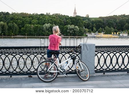 Woman with a bicycle is standing on the embankment in Moscow.