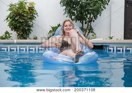 Young attractive woman lying on airbed laughing and relaxing with beer in pool.