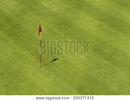 Golf hole with a flag from above.