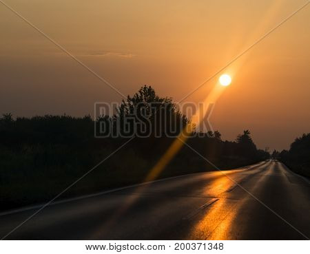 Long lonley road with a sunrise rising.