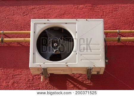 Used air conditioner on a red wall.