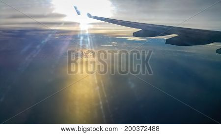 Flying high above clouds in late afternoon. Image features splashes of orange reflections caused by the sun, and flares caused by imperfections in the plane's window and internal reflections.