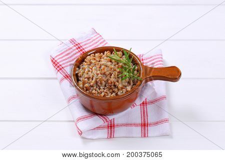 saucepan of cooked buckwheat on checkered dishtowel