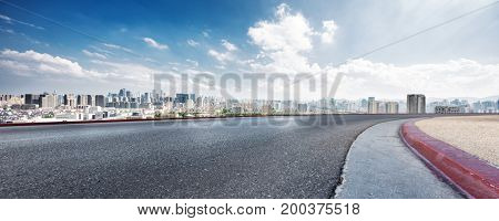 empty asphalt road with cityscape of hangzhou in cloud sky