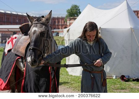 ST. PETERSBURG, RUSSIA - JULY 9, 2017: Man in medieval clothes prepares a horse for jousting during the military history project Battle On Neva at St. Peter and Paul fortress