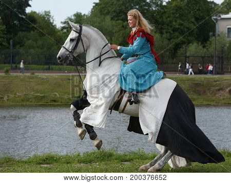 ST. PETERSBURG, RUSSIA - JULY 9, 2017: Women in medieval clothes on a horse during the military history project Battle On Neva. The main event this year is jousting tournament