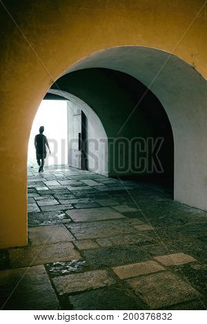Silhouette of a walking person in a tunnel of a building into the light
