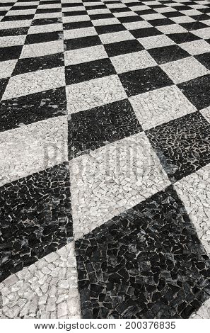 Detail of portuguese stone sidewalks with black and white checkered pattern