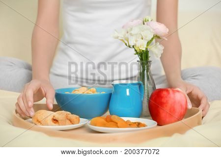 Young pretty woman having breakfast in bed at home