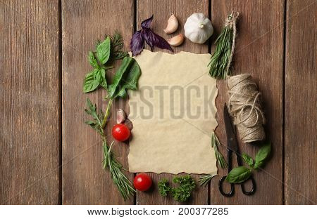 Frame made of various fresh herbs and vegetables on wooden background