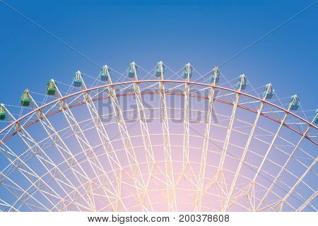 Amusement funfair giant ferris wheel with clear blue sky background