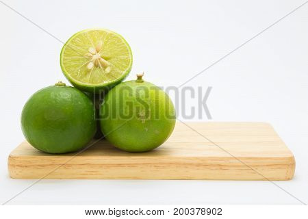 Slide fresh green limes on wooden board on white background
