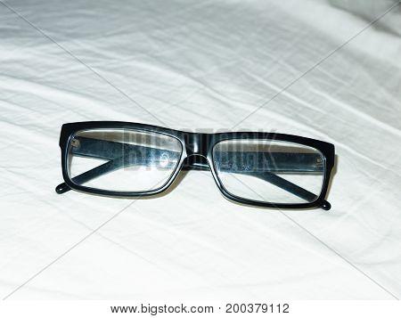 Folded Up Black Glasses Resting On White Bed Sheet