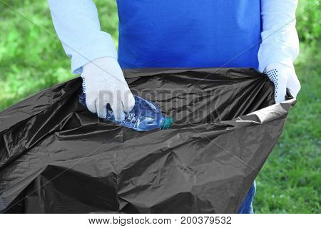 Young person gathering garbage in plastic bag. Volunteering concept