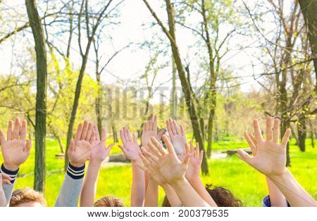 Young people putting hands in air together outdoors. Volunteering concept