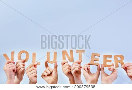 People putting hands in air together with word made of wooden letters on light background. Volunteering concept